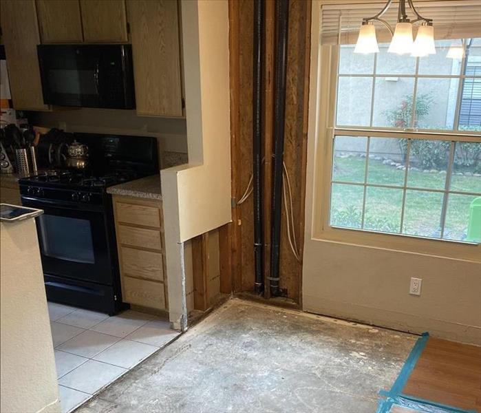 A photo of a condo with missing flooring and drywall.